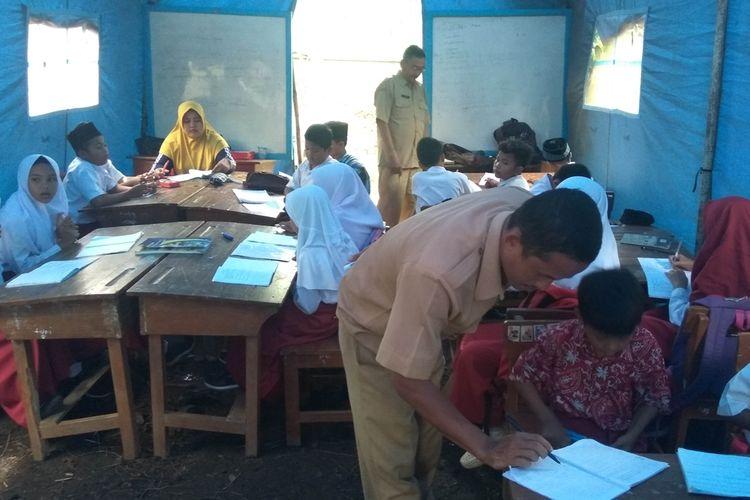Tiga guru mengajar muridnya di satu tenda, Rabu (6/11/2019). Para siswa terpaksa belajar di tenda karena ruang kelas SD Kadupandak 2 retak-retak terdampak pergerakan tanah di Dusun Sukamandi, Kecamatan Tambaksari, Kabupaten Ciamis.