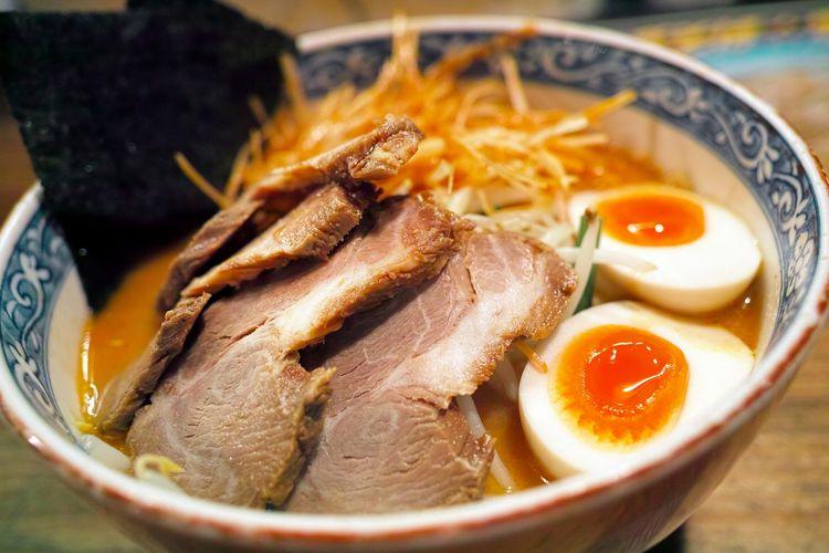 Ilustrasi ramen kuah miso dengan topping daging, sayuran, dan telur rebus.