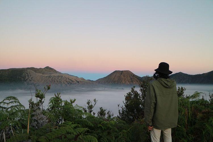 Wisatawan menikmati pemandangan saat berburu matahari terbit dari Bukit Mentigen, Cemoro Lawang, Desa Ngadisari, Sukapura, Probolinggo, Jawa Timur. Bukit Mentigen adalah salah satu alternatif tempat melihat matahari terbit selain Bukit Penanjakan di Taman Nasional Bromo Tengger Semeru.