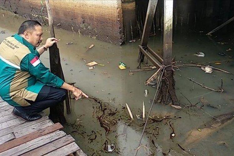Kepala Dinas Lingkungan Hidup Kota Banjarmasin, Mukhyar menunjukkan oli yang mencemari sungai Martapura di Siring Jalan Kapten Piere Tendean.