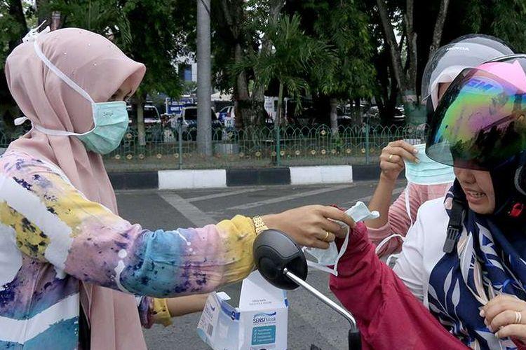 Relawan peduli kabut asap membagikan seribu masker kepada pengguna kendaraan di depan Masjid Raya Baiturrahman, Banda Aceh, Senin (23/9/2019). Berdasarkan data yang dirilis Badan Penanggulangan Bencana Aceh (BPBA) saat ini sembilan kabupaten di Aceh mengalami kondisi paparan kabut asap yang mulai parah, bahkan jarak pandang di dua kabupaten yang berada di perbatasan Sumut yaitu Kota Langsa dan Aceh Tamiang hanya berkisar 100-300 meter.
