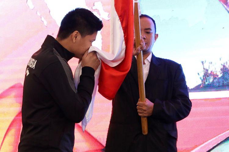 Pebulu tangkis ganda campuran Indonesia, Praveen Jordan, mencium bendera Indonesia saat acara pelepasan menuju Piala Sudirman 2019.