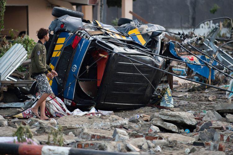 Seorang lelaki mencari barang-barang dari rumahnya yang rusak di Palu, Sulawesi Tengah, Sabtu (29/9/2018), setelah gempa kuat dan tsunami melanda daerah itu sehari sebelumnya. Hampir 400 orang tewas ketika gempa dan tsunami di Kota Palu.