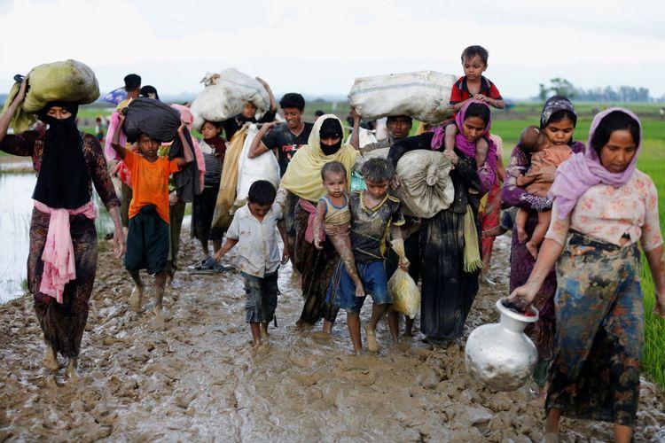 Sekelompok pengungsi Rohingya berjalan di jalan berlumpur setelah melewati perbatasan Bangladesh-Myanmar di Teknaf, Bangladesh, Jumat (1/9/2017).