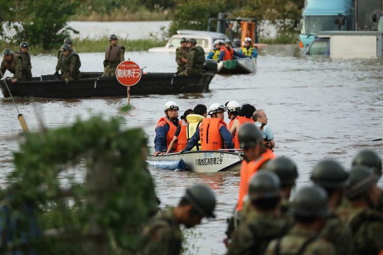 Petugas penyelamat, yang terdiri dari pemadam kebakaran dan tentara, membantu proses evakuasi penduduk dari daerah banjir di Kawagoe, prefektur Saitama, Minggu (13/10/2019).