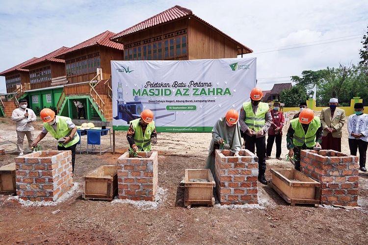 Proses peletakan batu pertama sebagai tanda diresmikannya pembangunan Masjid Az Zahra di kawasan wakaf Pusat Belajar Mengaji (PBM) Cahaya Negeri, Kecamatan Abung Barat, Kabupaten Lampung Utara, Lampung, Rabu (15/8/2021).