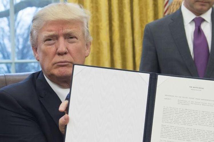 Presiden AS Donald Trump memperlihatkan perintah eksekutif yang mengeluarkan AS dari kerjasama trans-pasifik (TPP). Keputusan ini ditandatangani Trump di Ruang Oval, Senin (23/1/2017).
