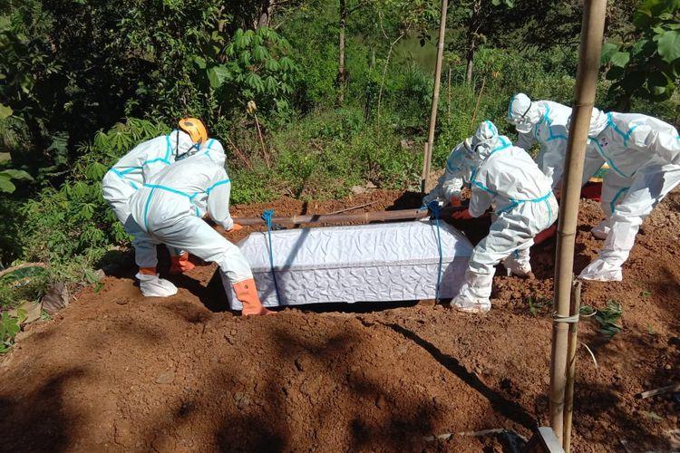 MAKAMKAN—Salah satu tim relawan BPBD Wonogiri memakamkan jenazah secara protokol kesehatan covid-19 di Desa Sonoharjo, Kecamatan Wonogiri, Kabupaten Wonogiri, Jawa Tengah,.