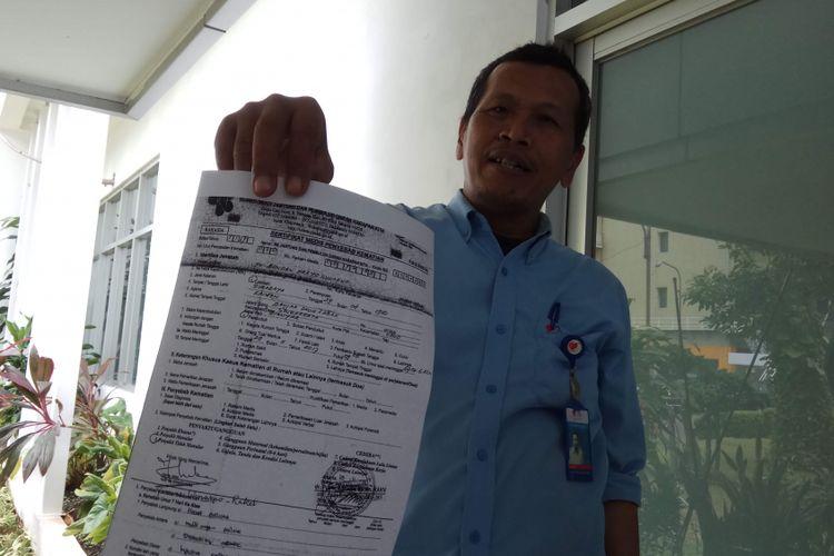 Petugas pelayanan jenazah rumah duka RS Harapan Kita, Jakarta, Sumanto ketika menunjukkan sertifikat medis penyebab kematian di rumah duka RS Harapan Kita Jakarta, Rabu (29/11/2017).