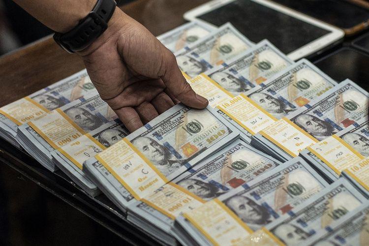 Petugas kepolisian menunjukkan barang bukti mata uang dolar palsu saat rilis pengungkapan kejahatan mata uang palsu di Bareskrim Mabes Polri, Jakarta, Kamis (23/9/2021). Direktorat Tindak Pidana Ekonomi dan Khusus (Dittipideksus) Bareskrim Polri berhasil mengungkap kejahatan uang palsu dengan barang bukti berupa 48 lak mata uang dolar palsu, 138 lak mata uang rupiah palsu dan alat pembuatnya serta mengamankan 20 orang tersangka di lima wilayah berbeda. ANTARA FOTO/Aprillio Akbar/foc.