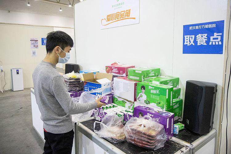 Pasien dengan gejala ringan virus corona COVID-19 mengambil makanan saat menjalani perawatan di sebuah pusat pameran yang diubah menjadi rumah sakit darurat di Wuhan, Hubei, China (17/2/2020). Data hingga Rabu (19/2/2020) ini, korban meninggal akibat virus corona di China sudah mencapai 2.000 orang setelah dilaporkan 132 kasus kematian baru.