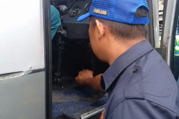 Petugas Dinas Perhubungan menekan pedal rem bus AKDP untuk mengecek kelayakan bus di Pangandaran, Kamis (20/12/2018).