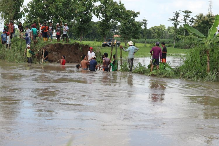 Upaya penanganan tangul sungai yang jebol dan menjadi banjir di Dusun Brangkal, Desa Brangkal, Kecamatan Bandar Kedungmulyo, Kabupaten Jombang, Jawa Timur, Sabtu (29/2/2020).