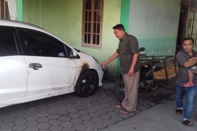 Kondisi mobil jenis MPV milik Sulaiman (54), warga Desa Peterongan, Kecamatan Peterongan, Kabupaten Jombang, Jawa Timur. Mobil warna putih itu dilempar bom oleh orang misterius saat terparkir di halaman rumah pemiliknya, Minggu (21/7/2019) dinihari.