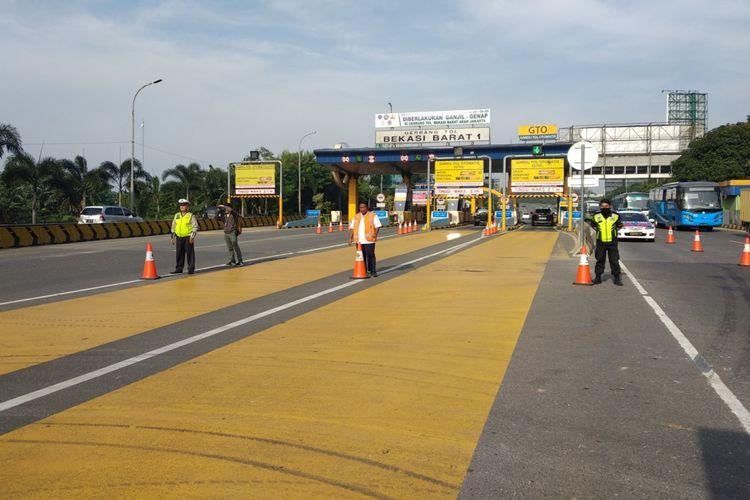 Petugas berjaga di depan gerbang tol Bekasi Barat dalam rangka pengawasan kebijakan ganjil genap