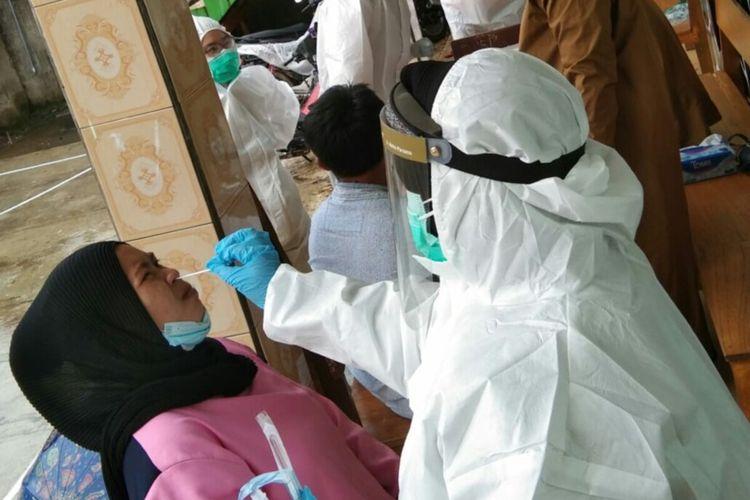 Petugas medis saat melakukan swab test antigen terhadap seorang pengungsi korban tanah longsor di Desa Cibokor, Cibeber, Cianjur, Kamis (17/6/2021). Hasilnya, sebanyak 56 orang terkonfirmasi positif Covid-19. Jumlahnya terus bertambah menjadi 76 orang pada Senin (21/6/2021).
