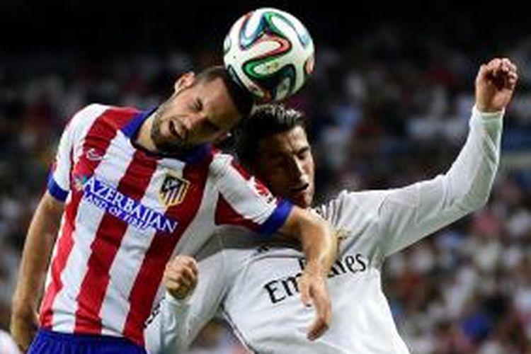 Bomber Real Madrid, Cristiano Ronaldo, berebut bola dengan gelandang Atletico Madrid, Mario Suarez, pada leg pertama Piala Super Spanyol 2014 di Santiago Bernabeu, Selasa atau Rabu (20/8/2014) pagi WIB.