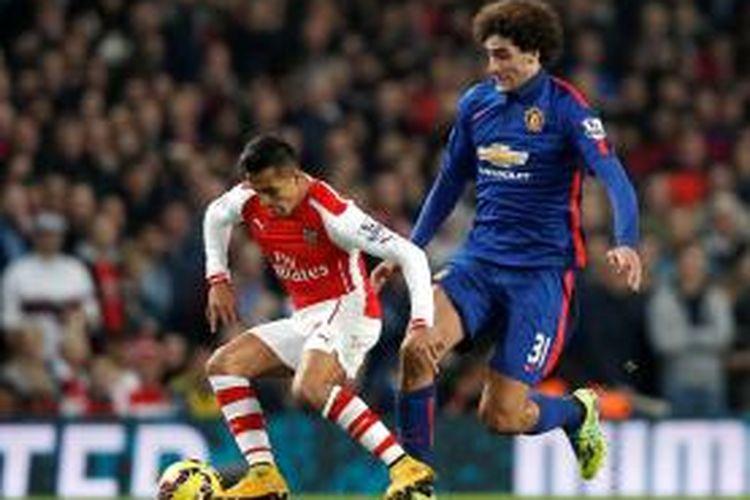 Striker Arsenal, Alexis Sanchez, saat mengamankan bola dari hadangan gelandang Manchester United, Marouane Fellaini, pada lanjutan Premier League di Emirates, Sabtu (22/11/2014).