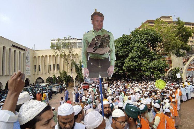 Para pendukung Islami Andolan Bangladesh, sebuah partai politik Islam, membawa guntingan foto Presiden Perancis Emmanuel Macron dengan kalung di sekelilingnya saat mereka memprotes penerbitan karikatur Nabi Muhammad yang mereka anggap menghujat, di Dhaka, Bangladesh, Selasa (27/10/2020). Muslim di Timur Tengah dan sekitarnya pada Senin menyerukan boikot produk Perancis dan protes atas karikatur, tetapi Macron telah berjanji negaranya tidak akan mundur dari cita-cita sekuler dan pembelaan kebebasan berbicara.