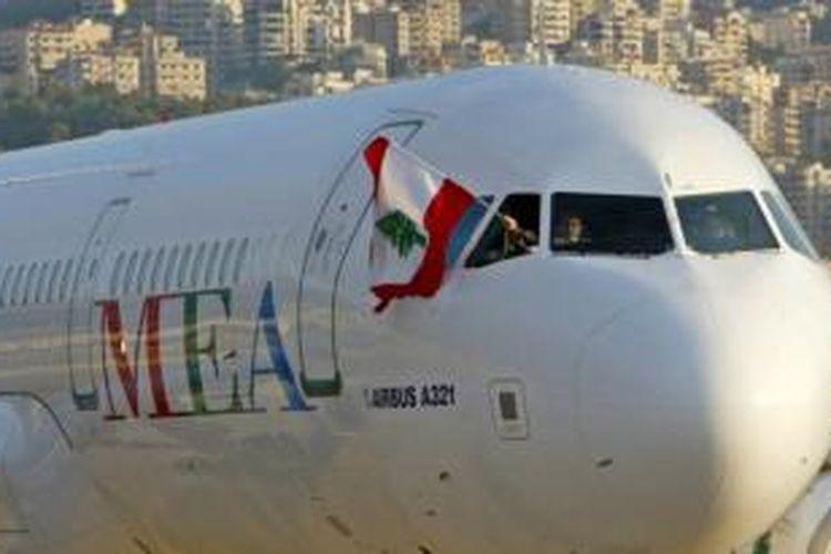 Seorang kru Middle East Airlines (MEA) mengibarkan bendera Lebanon saat mendarat di bandara internasional Beirut.