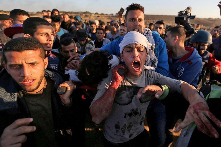 Seorang warga Palestina yang terluka diangkat warga saat aksi protes dan bentrok dengan pasukan Palestina dalam seruan Hari Kemarahan sebagai respons atas pengakuan Yerusalem sebagai ibu kota Israel oleh Presiden Amerika Serikat Donald Trump, dekat perbatasan dengan Israel di Jalur Gaza, Jumat (8/12/2017).