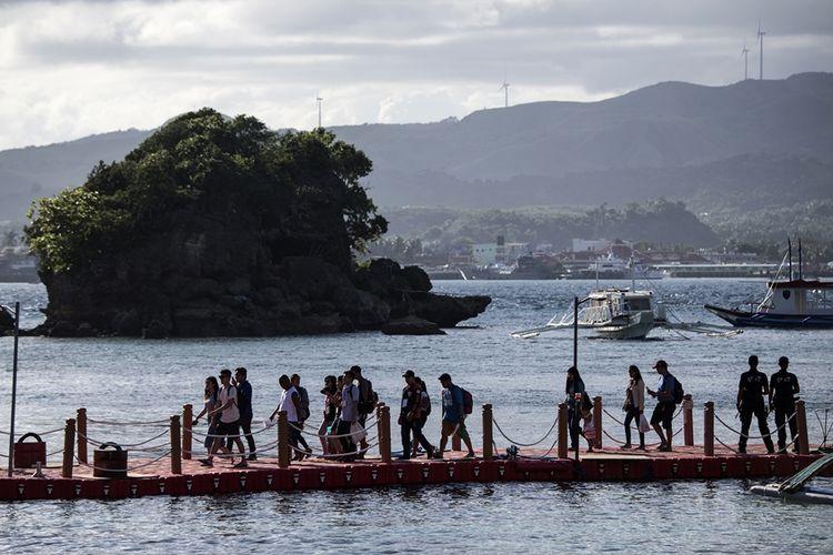 Para turis berjalan di dermaga saat tiba di Pulau Wisata Boracay, Filipina, yang kembali dibuka pada Jumat (26/10/2018), setelah enam bulan ditutup.