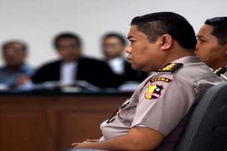 AKBP Teddy Rusmawan (kanan) memberikan kesaksian dalam sidang mantan Kakorlantas Mabes Polri Irjen Djoko Susilo (kiri) di Pengadilan Tindak Pidana Korupsi (Tipikor), Jakarta, Selasa (28/5/2013). Selain saksi AKBP Teddy Rusmawan hadir pula AKBP Wandi Rustiawan, Khadijah, Ni Nyoman Suhartini, Endah Purwaningsih, dan Brigjen (Pol) Didik Purnomo. Teddy menyatakan pernah diperintahkan Irjen Djoko Susilo saat menjabat sebagai Kakorlantas Polri untuk menyerahkan uang kepada oknum anggota Badan Anggaran DPR sebanyak empat kardus