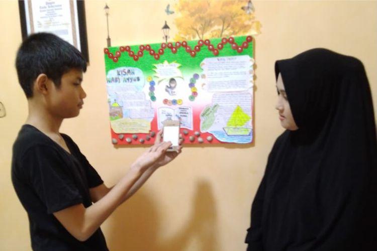Ihsan Budi Sastra, siswa kelas VI MI Muhammadiyah 1 Pekanbaru Riau, mempresentasikan hasil bacaan dipajang di mading kepada orangtuanya