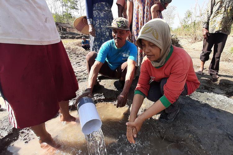 Suyadi (berkaus biru) bersama warga memanfaatkan air bersih yang tiba-tiba keluar dari ladang tandus di Widoro Lor, Desa Bendung, Semin, Gunungkidul, Yogyakarta, Rabu (21/8/2019).