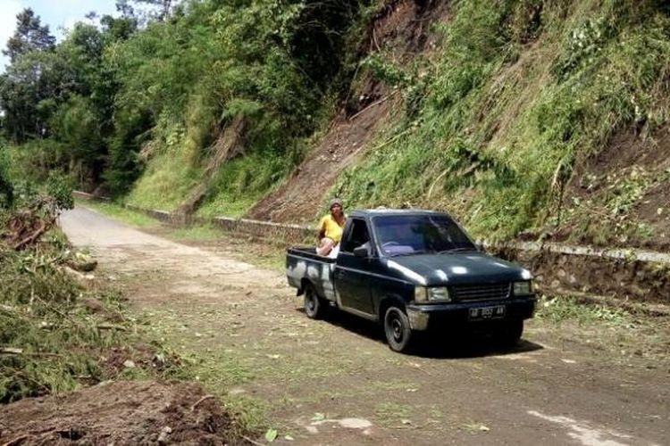 Sebuah mobil saat melintas di lokasi bekas longsoran tebing setinggi 20 meter di Dusun Turgo.
