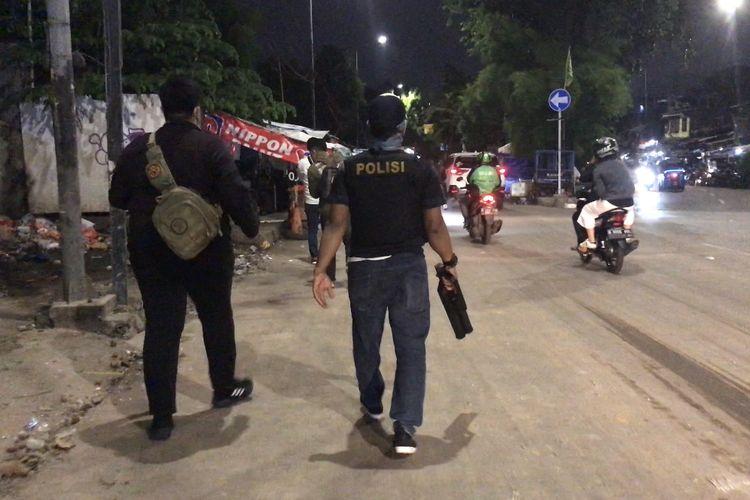 Polisi membawa senjata gas air mata untuk membubarkan warga yang terlibat tawuran di kawasan Manggarai, Tebet, Jakarta Selatan pada Senin (18/1/2021) malam.