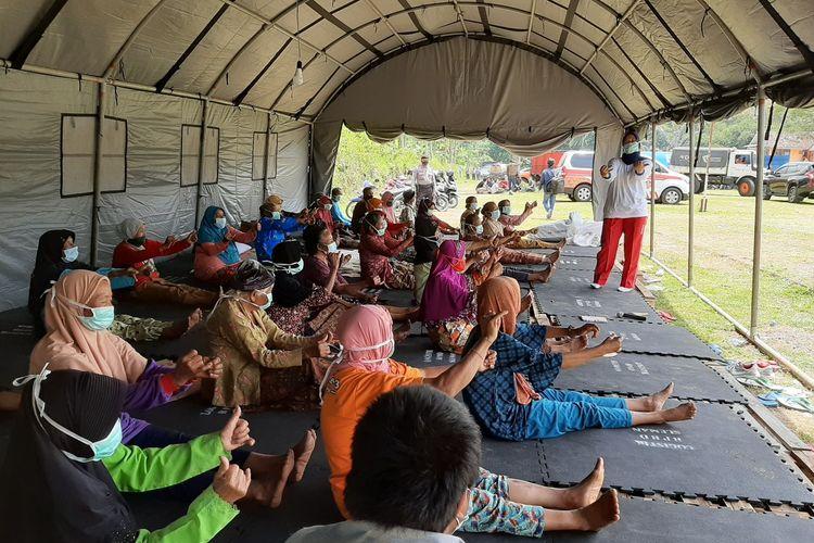 Para pengungsi saat mengikuti kegiatan senam pagi di barak pengungsian Glagaharjo, Cangkringan, Sleman