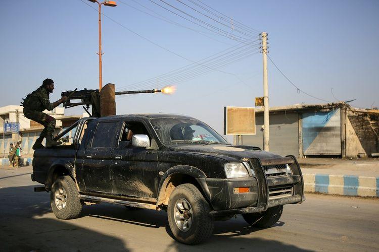 Pasukan milisi Suriah yang didukung Turki menembakkan senapan mesin di kota perbatasan Tal Abyad, Minggu (13/10/2019).