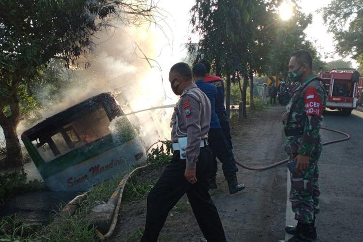 Petugas saat melakukan proses pemadaman api yang membakar bus AKDP Sinar Mandiri, Rabu (24/3/2021).