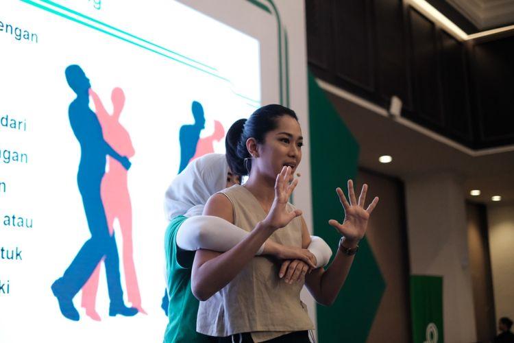Bungsu Widowati (kiri), Area Head of Sales GrabFood Sulawesi & Kalimantan dan Pelatih Taekwondo dan Prisia Nasution (kanan), Aktris dan Atlet Pencak Silat, saat mendemonstrasikan gerakan bela diri dasar ke 100 mitra pengemudi Grab Jabodetabek di Jakarta, Senin (22/4/2019).