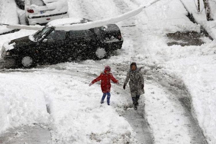 Dua anak di Teheran, Iran berjalan di antara salju yang bertumpuk di jalanan.