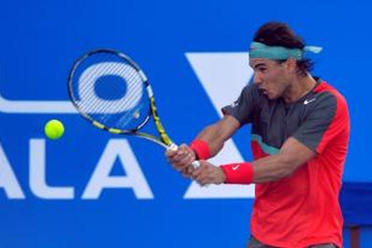 Petenis Spanyol, Rafael Nadal mengembalikan bola ke arah David Ferrer yang juga berasal dari Spanyol, pada babak semifinal Mubadala World Tennis Championship di Abu Dhabi, 27 Desember 2013.