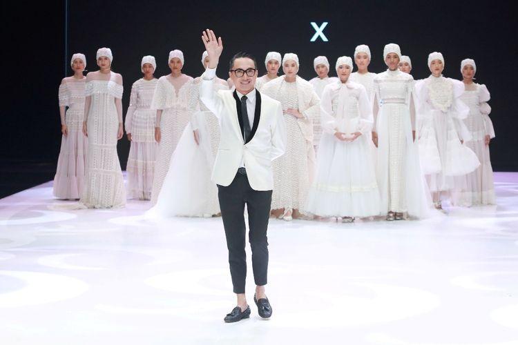 Desainer Barli Asmara bersama busana rancangannya di Indonesia Fashion Week 2019.