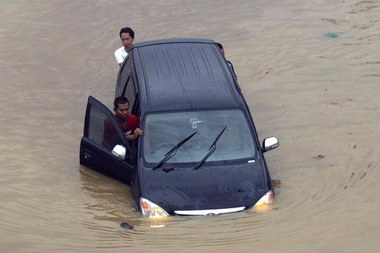 Caption : Luapan Kali Ciliwung memutus jalur kendaraan di Jalan KH Abdullah Syafiie, Tebet, Jakarta Selatan, Senin (13/1/2014). Luapan kali mulai menggenangi permukiman dan memutus jalan sejak Senin dini hari. KOMPAS/AGUS SUSANTO