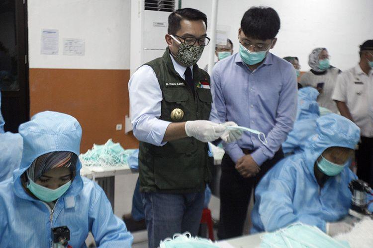 Gubernur Jawa Barat Ridwan Kamil (kiri) melihat produksi  pembuatan masker medis di PT Multi One Plus, Gunung Putri, Kabupaten Bogor,  Jawa Barat, Rabu (15/4/2020). Kunjungan Gubernur tersebut untuk memastikan ketersediaan Alat Pelindung Diri (APD) bagi kebutuhan Jawa Barat dan nasional.