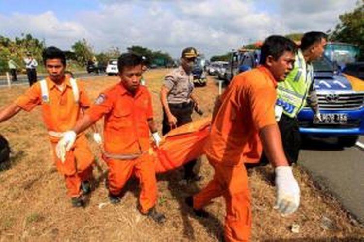Petugas mengevakuasi korban kecelakaan bus Rukun Sayur dengan nomor polisi AD 1523 CF di kilometer 202 Tol Palimanan - Kanci, Cirebon, Jawa Barat, Selasa (14/7/2015). Sebanyak 11 orang meninggal dunia dalam kecelakaan ini.
