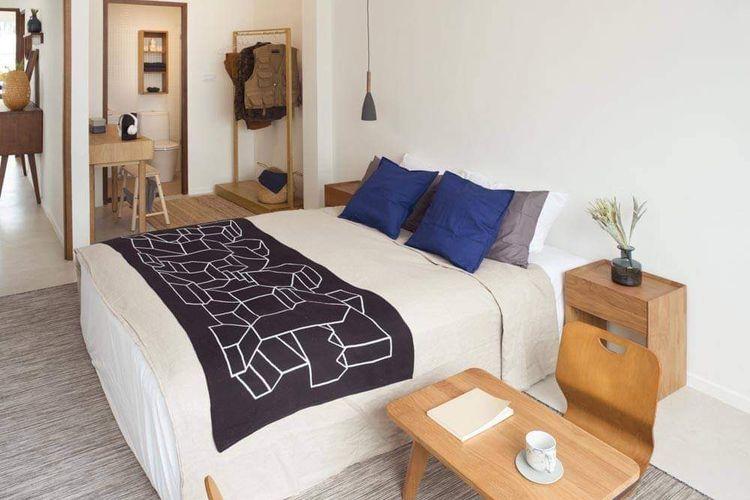 Kamar tidur dengan corak coklat dan berbagai kombinasi warna tebal.