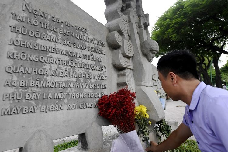 Seorang warga Vietnam meletakkan bunga sebagai penghormatan kepada mendiang Senator AS John McCain di memorial Perang Vietnam di dekat Danau Truc Bach, Minggu (26/8/2018).
