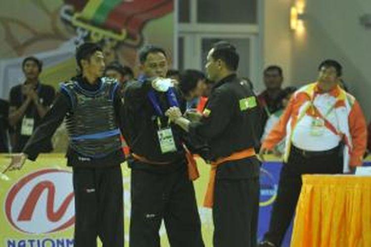 Kontingen silat Myanmar memprotes kepustusan wasit yang memenangkan pesilat Indonesia Mohammad Adhan Rusdin (kiri) yang bertarung melawan pesilat tuan rumah SEA Games 2013 Myanmar Ye Kyaw Thu di stadion tertutup Zayar Thiri, Napyitaw, Myanmar, Minggu (15/12). Adhan memenangi pertarungan nomor tarung 55-60 kilogram tersebut dan berhak dikalungi medali emas.