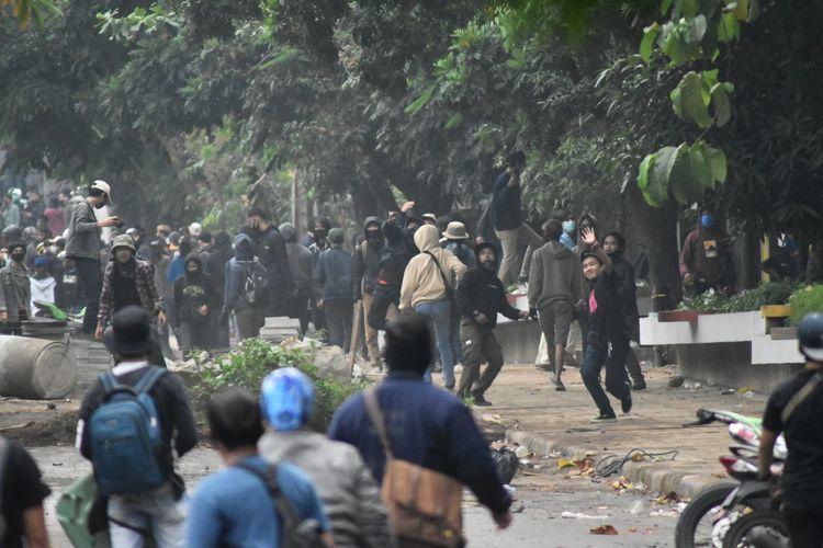 Tampak massa aksi melakukan pelemparan batu terhadap para petugas saat pengawalan Demo Tolak UU Omnisbuslaw Cipta Kerja di Gedung DPRD, Kamis (8/10/2020), hal tersebut mengakibatkan kericuhan dan kerusakan sejumlah fasilitas umum di sekitar lokasi demo.