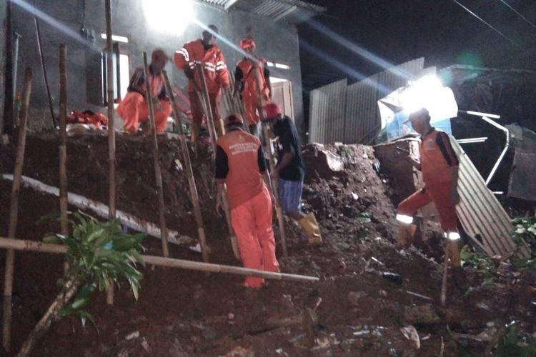 Petugas PPSU sedang membersihkan puing longsoran dan memasang turap sementara bagian depan rumah milik seorang warga di Jalan Agung Raya 2 Gang Swadaya 2 RT 005/04, Lenteng Agung, Jagakarsa, Jakarta, Kamis (13/8/2020) yang longsor pukul 16.00 WIB.