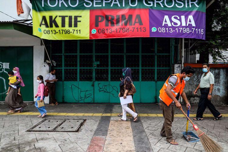 Seorang warga menyapu di trotoar jalan karena tidak menggunakan masker saat patroli penegakan aturan pembatasan sosial berskala besar (PSBB) di Jl. Matraman Raya, Kecamatan Jatinegara, Jakarta Timur, Selasa (19/5/2020). Dalam kegiatan patroli PSBB tersebut, target penegakan untuk masyarakat yang tidak mengunakan masker dijalanan.