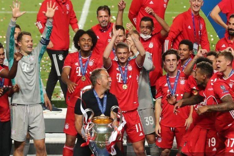 Pelatih Bayern Muenchen Hans-Dieter Flick bersama para pemainnya merayakan trofi juara Liga Champions yang mereka raih seusai mengalahkan PSG pada laga final, 23 Agustus 2020.