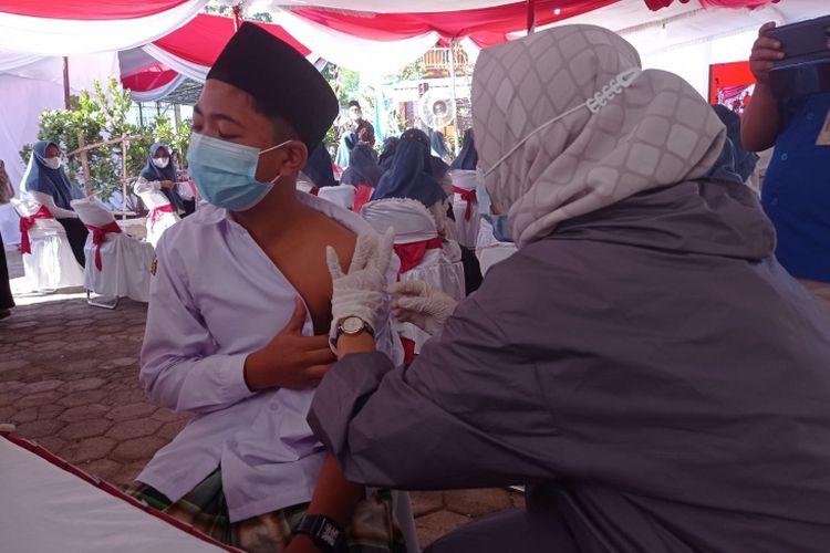 Seorang santri di Pondok Pesantren Al Masudiyyah mendapat suntikan vaksinasi Covid-19.