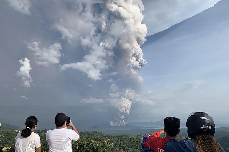 Warga melihat Gunung Berapi Taal yang meletus dari Kota Tagaytay, Filipina, Minggu (12/1/2020). Setidaknya 10.000 orang dilaporkan mengungsi setelah Gunung Taal  meletus dan pemerintah setempat mengumumkan menaikkan level peringatan ke tingkat tertinggi kedua, dengan letusan dahsyat bakal terjadi dalam hitungan jam hingga hari.